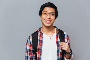 Portrait of a smiling asian man in glasses with backpack standing and looking at camera isolated on the gray background