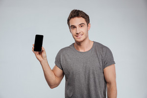 Portrait of a smiling attractive man holding blank screen smartphone over white background
