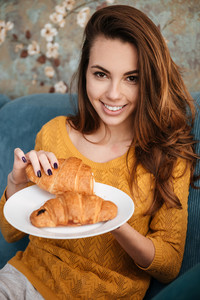 Portrait of a smiling attractive woman eating croissant on a plate while sitting on the couch indoors