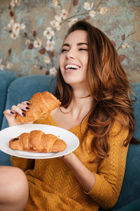 Portrait of a smiling attractive woman holding plate with croissants and laughing while sitting on the couch indoors