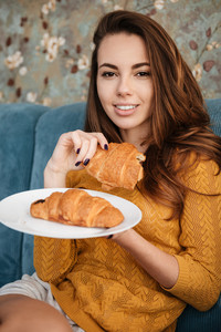 Portrait of a smiling attractive woman holding plate with croissants while sitting on the couch indoors