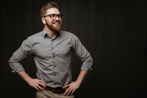 Portrait of a smiling bearded man in eyeglasses standing with hands on hips and looking away isolated on the black wooden background