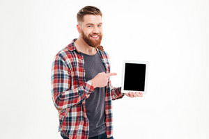 Portrait of a smiling bearded man pointing finger on blank tablet computer screen isolated on a white background