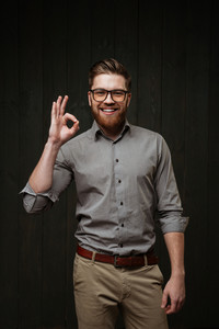 Portrait of a smiling bearded man wearing eyeglasses and shirt and showing okay gesture isolated on the black wooden background
