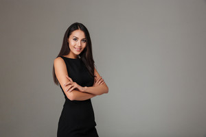 Portrait of a smiling beautiful woman in black dress standing with arms folded isolated on a gray background