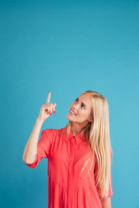 Portrait of a smiling blonde girl pointing finger up at copyspace isolated on a blue background