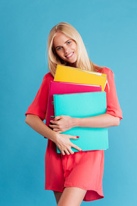 Portrait of a smiling blonde woman in red dress holding colorful folders over blue background
