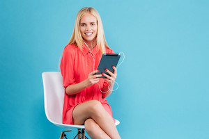 Portrait of a smiling blonde woman in red dress listening music and holding tablet isolated on the blue background