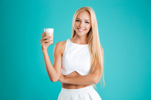 Portrait of a smiling blonde woman looking at camera and drinking coffee to go isolated on the blue background
