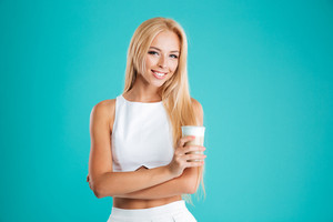 Portrait of a smiling blonde woman with long hair drinking coffee to go isolated on the blue background