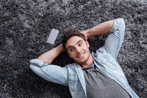 Portrait of a smiling casual man lying on the carpet with mobile phone at home