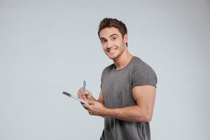 Portrait of a smiling casual man making notes in notepad with pen and looking at camera over white background
