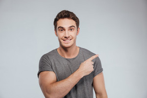 Portrait of a smiling casual man pointing finger away over white background