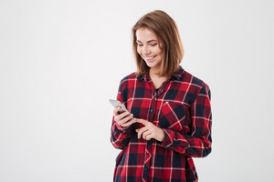 Portrait of a smiling casual woman holding smartphone over white background