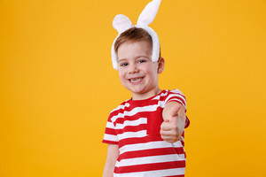 Portrait of a smiling cheerful little boy wearing rabbit ears and showing thumbs up isolated over orange background