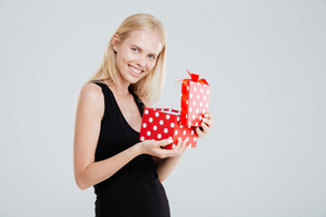 Portrait of a smiling cheerful woman in dress opening gift box isolated on a white background