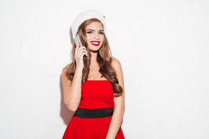 Portrait of a smiling cheerful young woman in red dress and hat talking on mobile phone and looking at camera isolated on the white background