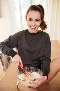 Portrait of a smiling cute girl blending eggs and flour in glass bowl with whist while sitting on a kitchen table