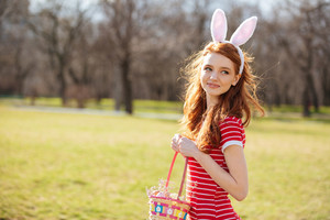 Portrait of a smiling cute red head girl wearing bunny ears and holding basket full of easter eggs outdoors