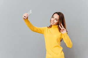 Portrait of a smiling cute woman making selfie photo on smartphone over gray background