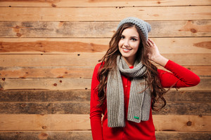Portrait of a smiling cute woman with scarf and hat standing over wooden background and looking at camera