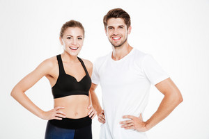 Portrait of a smiling fitness couple standing with hands on hips isolated on a white background