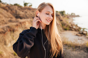 Portrait of a smiling fitness woman with eyes closed listening music with earphones outdoors at the beach