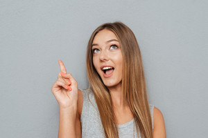 Portrait of a smiling girl pointing finger up at copyspace isolated on a gray background