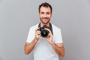 Portrait of a smiling handsome man holding camera isolated on a gray background