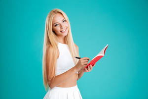 Portrait of a smiling happy girl making notes in notebook isolated on the blue background