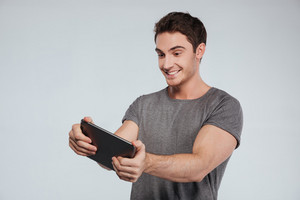 Portrait of a smiling happy man using tablet computer isolated on a white background