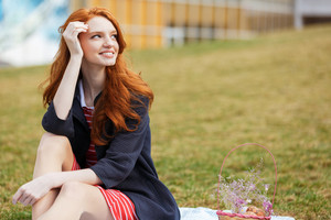 Portrait of a smiling happy red head girl having easter picnic with basket and eggs while sitting on the grass in park