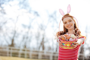 Portrait of a smiling happy red head girl wearing bunny ears and showing basket with painted easter eggs outdoors