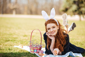 Portrait of a smiling happy red head girl wearing easter bunny ears and laying on a grass with basket full of painted eggs