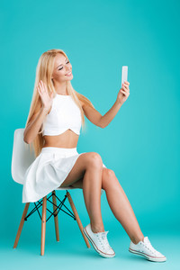 Portrait of a smiling happy woman sitting on chair with mobile phone and waving