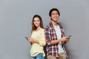 Portrait of a smiling interracial couple standing and holding mobile phones isolated on the gray background