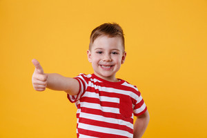 Portrait of a smiling little boy showing thumbs up isolated over orange background