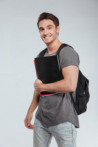 Portrait of a smiling male student with backpack and folders over white background