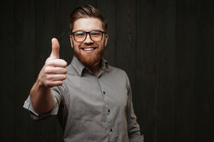 Portrait of a smiling man in glasses showing thumb up isolated on the black wooden background