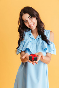 Portrait of a smiling pretty woman in blue dress holding jewellery box isolated on the orange background