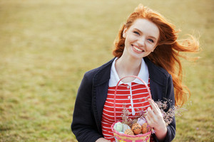 Portrait of a smiling red head girl with long hair holding easter picnic basket with eggs and looking at camera while resting in park