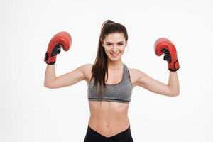 Portrait of a smiling satisfied sports woman wearing boxing gloves and showing biceps isolated on a white background