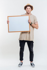 Portrait of a smiling stylish man holding blank board isolated on the white background
