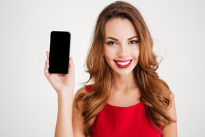 Portrait of a smiling woman in red dress showing blank smartphone screen isolated on a white background