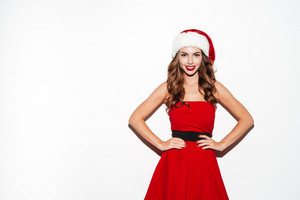 Portrait of a smiling woman in santa claus cloth standing holding hands on hips isolated on a white background
