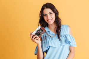 Portrait of a smiling young brunette girl holding photo camera isolated on a orange background