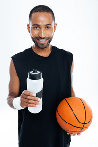 Portrait of a smiling young handsome sportsman holding basket ball and water bottle isolated on a white background