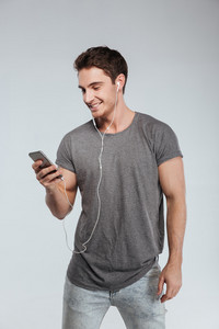 Portrait of a smiling young man listening to music from smartphone over white background