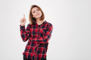 Portrait of a smiling young woman in plaid shirt pointing finger up and looking away isolated on the white background