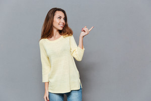Portrait of a smiling young woman in sweater pointing finger away isolated on the gray background